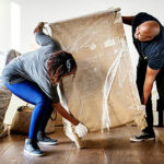 Couple moving a piece of wooden furniture